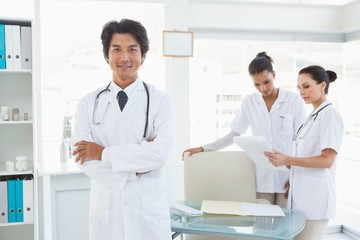 Doctor smiling in front of work colleagues