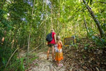 Mother and daughter read information from poster at hiking trail