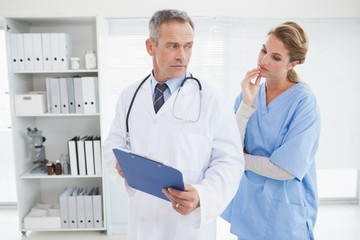 Serious doctor showing nurse a chart