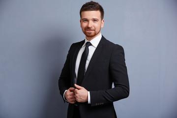 man adjusts his suit clothes