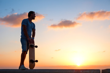 man with skateboard in sunset