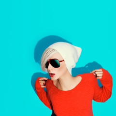 fashion blond girl with trendy hat and sunglasses on a blue back