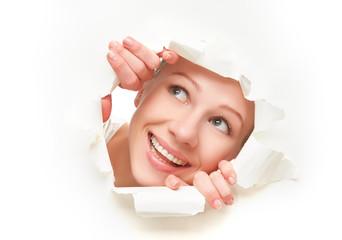 woman peeking through a  hole torn in white paper