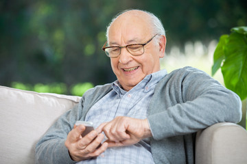 Smiling Senior Man Text Messaging Through Mobilephone