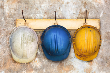 Three construction helmets hanging on a hat-rack