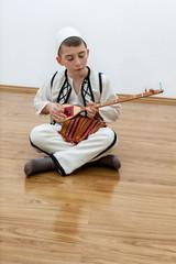 Sitzender Junge spielt Saiteninstrument