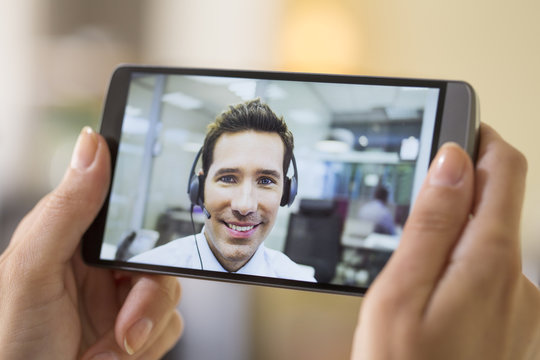 Female hand holding a smart phone during a Skype video
