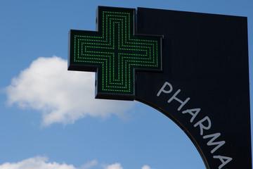 signe de pharmacie avec la croix verte en éclairage urbain