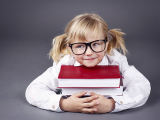 Adorable little girl wearing glasses and  holding books