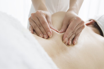 Esthetician pinching the flab on the back