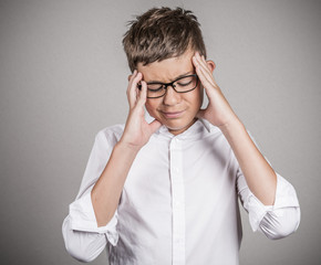 Stressed teenager boy with headache on grey background