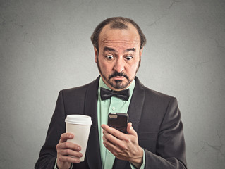 surprised man reading news on smartphone drinking coffee
