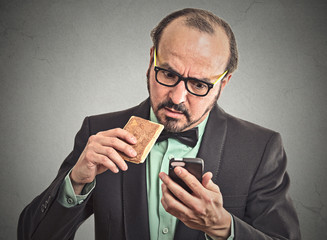 man reading message on smart phone eating cookie