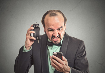 angry businessman with alarm clock looking at smartphone