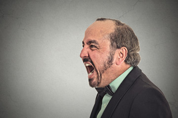 side profile portrait angry man screaming on grey background