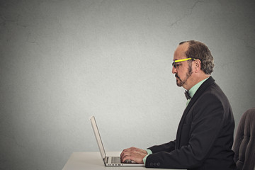 business man with glasses using laptop computer sitting at table