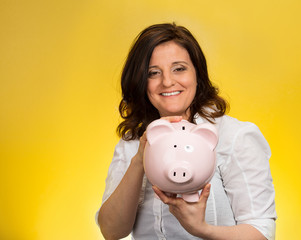 woman holding piggy bank yellow background with copy space