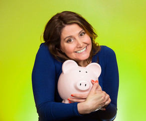 woman holding piggy bank isolated on green background