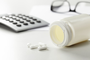 Pills, bottle and calculator against white background