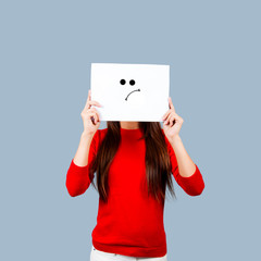 Girl holding a paper with a sad face painted Isolated on White