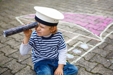 Little preschool child having fun with ship picture drawing with