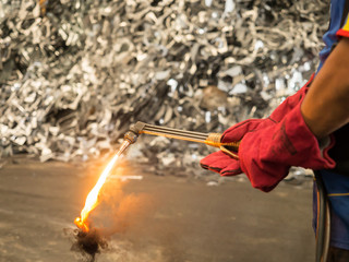 Metal cutting torch with soot and flame in recycle factory