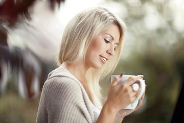 Beautiful woman drinking tea in the garden