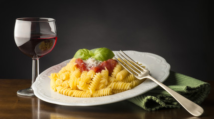 dish with macaroni and tomato sauce on the wooden table