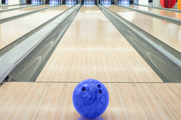 Balls on bowling alley against ten pins