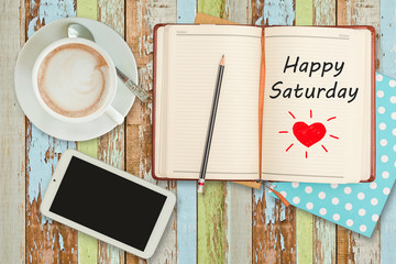 """Happy Saturday""on notebook with smart phone and coffee cup"