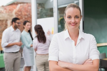 Blonde smiling businesswoman standing with arms crossed