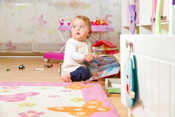 Kleinkind mit Buch im Kinderzimmer