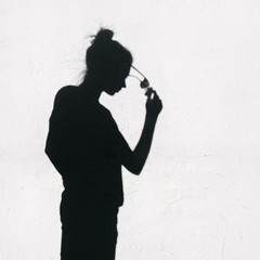 Girl with sunglasses around on wall background