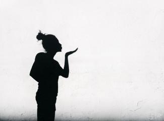 Girl sending air kiss around on white wall background