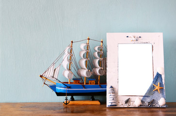 Vintage nautical frame  on wooden table. retro filtered image