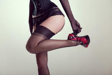 Pinup girl in vintage nylon stockings holding high heel shoe