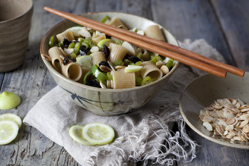 pasta thai with lime, almond, olive and green pepperoni on bowl