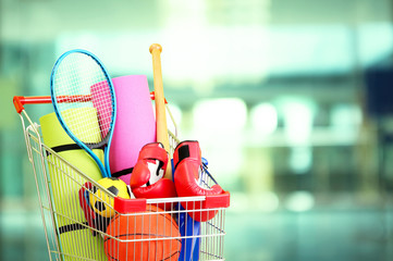 Shopping concept. Shopping cart with sport equipment