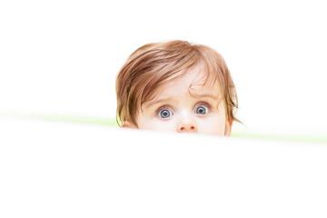 little cute baby peeking out of the bath.