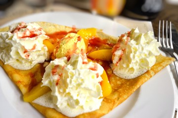 Sweet French crepe with whipped cream and peaches