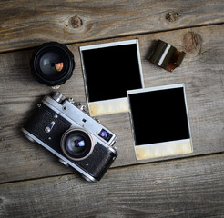Vintage camera with lenses and blank old photograph on wooden ba