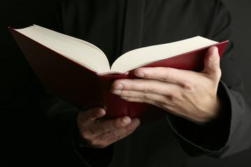 Man holding Bible on dark background