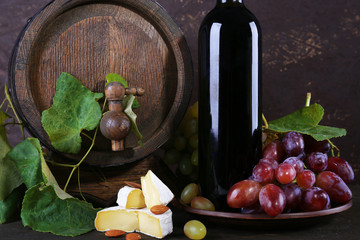 Wine in bottle and in goblet, Camembert cheese, grapes and