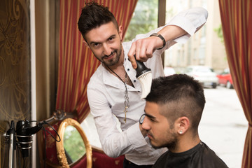 Hairdresser Cleaning Young Man After Haircut