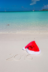 2016 written on tropical beach white sand with xmas hat