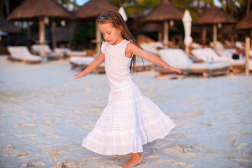 Adorable little girl have fun at sunset beach