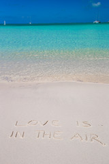 Love is in the air written on tropical beach white sand