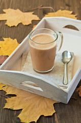 Cup of coffee  with milk on wooden background with autumn leaves