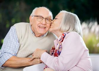 Senior Woman Kissing On Man's Cheek