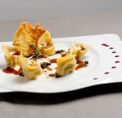 Italian homemade ravioli with cheese in a white plate